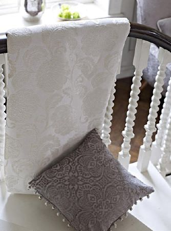 Prestigious Textiles -  Greenwich Fabric Collection - Subtly patterned ivory coloured floral fabric draped over a white and brown wood bannister, with a grey patterned cushion