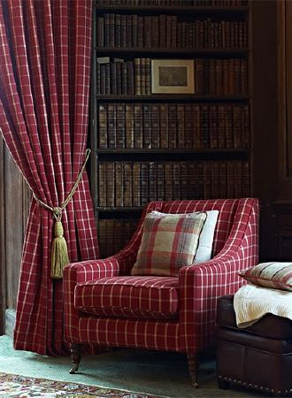 Prestigious Textiles -  Highland Fabric Collection - Simple creamy gold checks on burgundy coloured fabric curtains and an armchair, with a green tassel tieback and a cushion