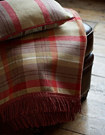 Prestigious Textiles -  Highland Fabric Collection - A brown leather case draped with a fringed throw and a cushion, both made inred, white, cream-beige and purple-grey checks