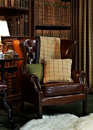 Prestigious Textiles -  Highland Fabric Collection - A creamy yellow cushion and throw with a red and grey grid, and a plain green cushion, on a dark brown leather armchair