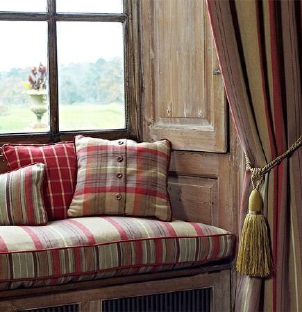 Prestigious Textiles -  Highland Fabric Collection - A red and white checked cushion on a window seat with striped and checked cushions and curtains in dusky red, beige and grey
