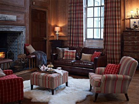 Prestigious Textiles -  Highland Fabric Collection - A leather sofa with red, white and beige checked and striped armchairs, cushions, curtains and a footstool with a fluffy rug