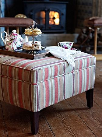 Prestigious Textiles -  Highland Fabric Collection - A footstool made with wooden legs and dusky beige, grey, red and white stripes, with a tea tray and floral crockery