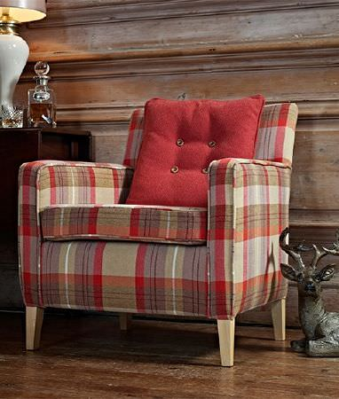 Prestigious Textiles -  Highland Fabric Collection - A red cushion with four buttons on ared, white, purple-grey and beige checked armchair with wooden feet, and a stag statue