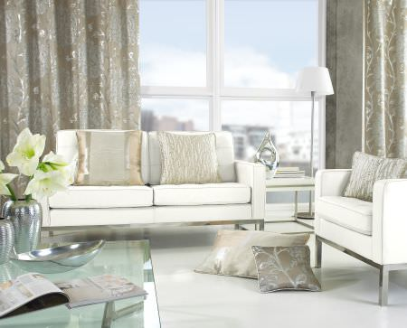 Prestigious Textiles -  Hollywood Fabric Collection - A modern living room with white upholstered couches with gold pillows and grey curtains decorated with vines giving them a modern look
