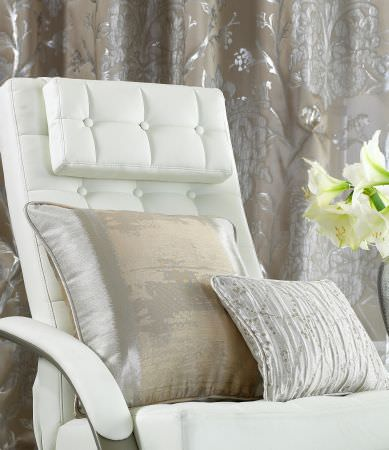 Prestigious Textiles -  Hollywood Fabric Collection - A white leather upholstered easy chair with two pillows, one in plain gold colour, the other with creases and dots
