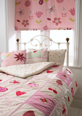 Prestigious Textiles -  Home Sweet Home Fabric Collection - Pink and white chequered quilt with simple fruit designs, pillows with dots and a pink roman blind with flowers for childrens rooms