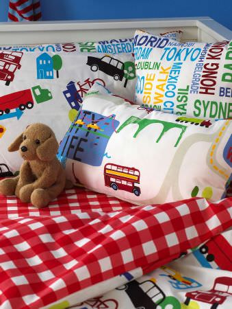 Prestigious Textiles -  Home Sweet Home Fabric Collection - White pillows with trucks, buildings. cars, and buses and with red tartan backs, and a cushion with the names of big cities for children