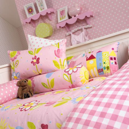 Prestigious Textiles -  Home Sweet Home Fabric Collection - Light pink bedspread and pillows with watercolour flower impressions, pink pillows with dots, and a pink tartan duvet for a girls bedroom