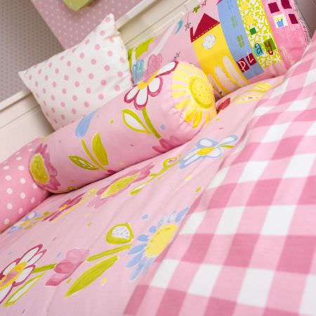 Prestigious Textiles -  Home Sweet Home Fabric Collection - Girls pink pillows with flower and building images or dots, a pink duvet with flowers and a pink tartan quilt for a joyful bedroom