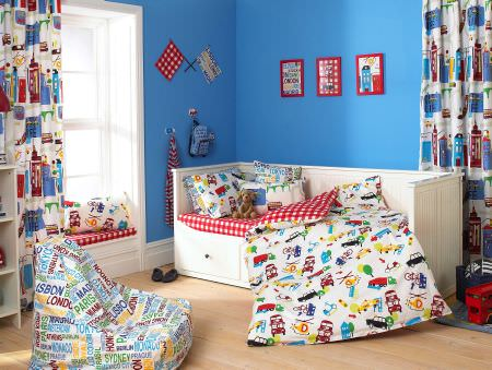 Prestigious Textiles -  Home Sweet Home Fabric Collection - Boys bedroom with a white duvet with trucks, cars and helicopters, a red plaid mattress cover, a white bean bag with names of big cities