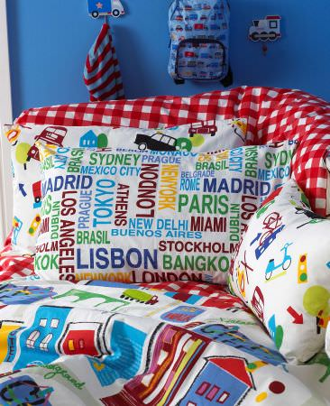 Prestigious Textiles -  Home Sweet Home Fabric Collection - Pillows with names of big cities, or cars, buildings and trucks, a white quilt with colourful buildings for a childrens bedroom