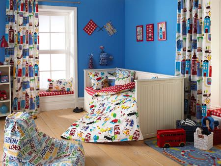 Prestigious Textiles -  Home Sweet Home Fabric Collection - Boys bedrooom with a bean bag, white curtains with colourful buildings, and pillows and a duvet with colourful cars and buildings