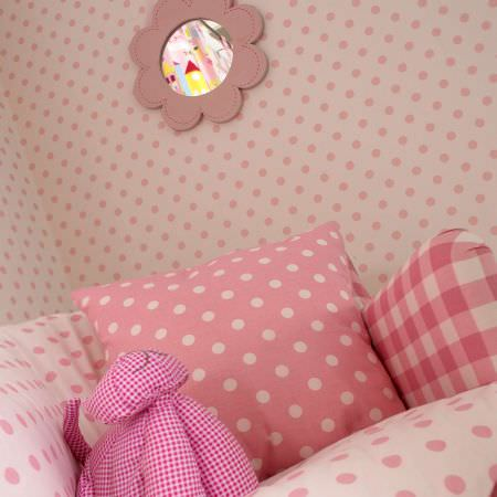 Prestigious Textiles -  Home Sweet Home Fabric Collection - Pink cushion with white dots and a white cushion with pink dots, on a white duvet with pink dots and dotted white fabric wallpaper