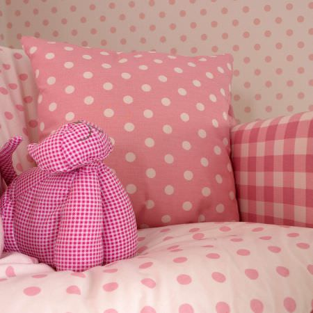 Prestigious Textiles -  Home Sweet Home Fabric Collection - Pink plaid and dotted pillows on a white quilt with pink dots, surrounded by white wallpaper with pink dots from the Home Sweet Home fabric