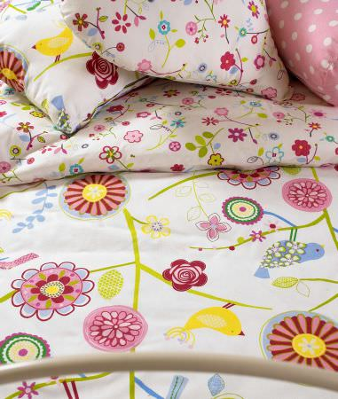 Prestigious Textiles -  Home Sweet Home Fabric Collection - White bedspread and pillow covers with modern abstract flower and bird impressions from the Home Sweet Home fabric collection