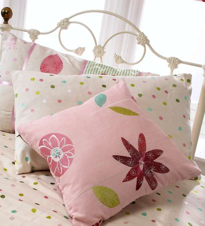 Prestigious Textiles -  Home Sweet Home Fabric Collection - An antique metal frame bed with a white duvet with colourful spots, pillows with spots, and cushions with flowers