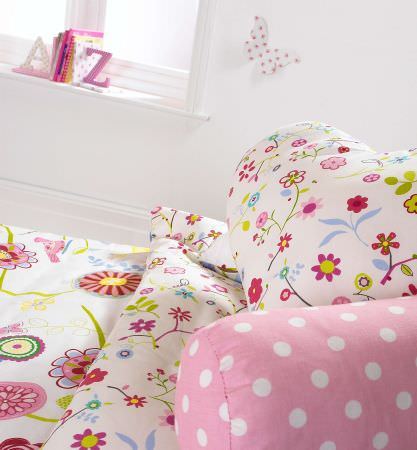 Prestigious Textiles -  Home Sweet Home Fabric Collection - A white quilt and pillow with modern abstract flower imagery, and a pink cushion with white dots
