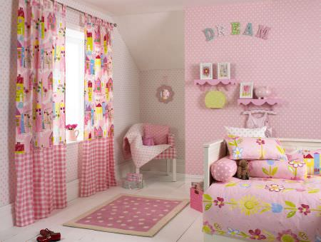 Prestigious Textiles -  Home Sweet Home Fabric Collection - Girls bedroom with pink curtains with colourful buildings and tartan bottom, a pink duvet with big flowers and flowery cushions