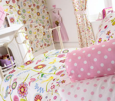 Prestigious Textiles -  Home Sweet Home Fabric Collection - White and pink pillows with dots or flowers, a white quilt with large flowers, and white fabric wallpaper with a colourful flower pattern