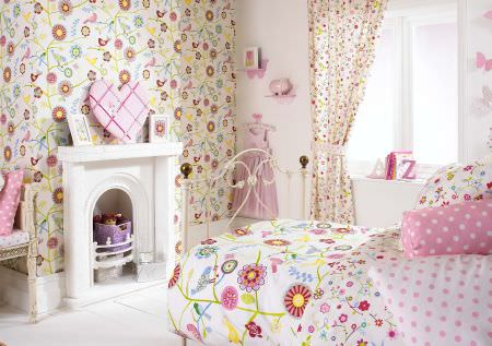 Prestigious Textiles -  Home Sweet Home Fabric Collection - A modern bedspread with large and small flowers, pink and white pillows with dots, and white curtains with flowers in an antique setting