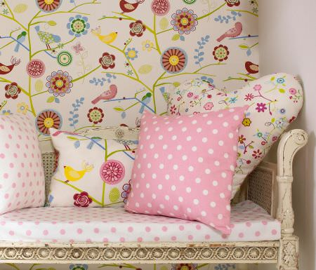 Prestigious Textiles -  Home Sweet Home Fabric Collection - Antique bench with a white seating pad with pink dots, and cushions with modern flower imagery or dots