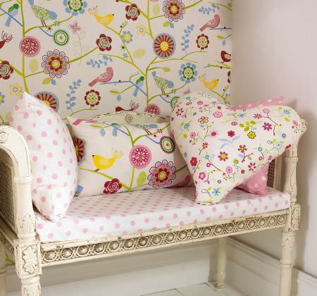 Prestigious Textiles -  Home Sweet Home Fabric Collection - An antique bench with a white dotted seating pad, a heart-shaped pillow with flowers and fabric wallpaper with modern flower and bird design