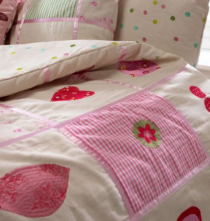 Prestigious Textiles -  Home Sweet Home Fabric Collection - Close-up photo of a white duvet with hearts, cherries and tartan patches and pillows with colourful dots