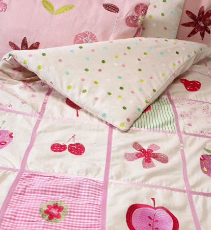 Prestigious Textiles -  Home Sweet Home Fabric Collection - White duvet with pink lines and cherry, flower, and tartan patches on one side, and dots on the other, with pink pillows with flowers