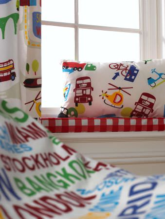 Prestigious Textiles -  Home Sweet Home Fabric Collection - A red and white tartan seating pad with a white pillow with buses and helicopters, and a white curtain with cars and roads for a boys room