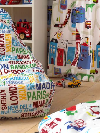 Prestigious Textiles -  Home Sweet Home Fabric Collection - White bean bag with names of big cities and a white curtain with iimages of buildings and helicopters for childrens rooms