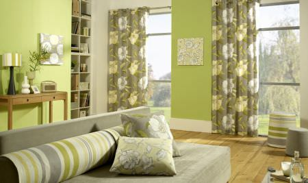 Prestigious Textiles -  Honolulu Chartreuse Fabric Collection - A modern house setting with a green upholstered couch with pillows with detailed flower impressions, and green curtains with flowers