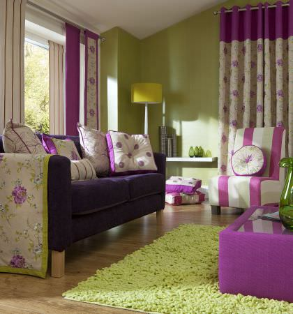 Prestigious Textiles -  Honshu Fabric Collection - Dark purple upholstered couch with large white cushions with purple edges, an upholstered coffee table and a modern chair with stripes