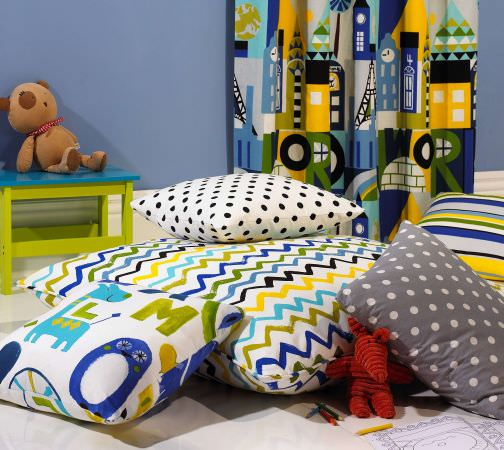 Prestigious Textiles -  Ideal World Fabric Collection - colourful animal, zigzag, striped and spotted cushion designs in blue, yellow, green, white and grey from the Ideal World Fabric Collection