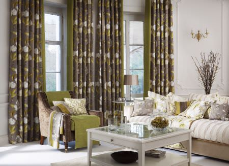 Prestigious Textiles -  Imperial Fabric Collection - Green curtains with detailed white floral impressions, a white striped upholstered couch with cushions and armchair in a modern setting