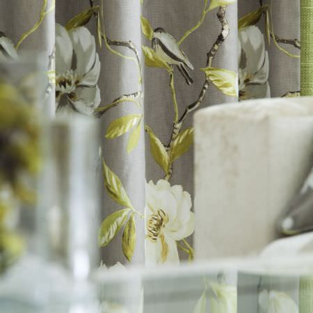 Prestigious Textiles -  Imperial Fabric Collection - Close-up shot of a grey curtain with classic white and green detailed watercolour flower design