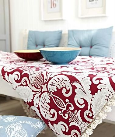 Prestigious Textiles -  Indigo Fabric Collection - Lace-edged patterned red and white tablecloth, two blue cushions, one blue cushions with cream lace detail, one red bowl and one blue bowl