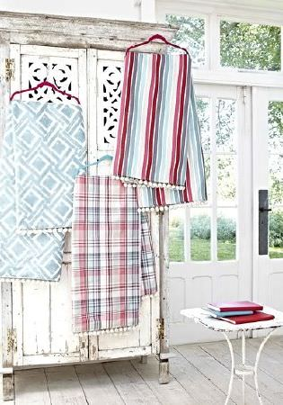 Prestigious Textiles -  Indigo Fabric Collection - Shabby chic wardrobe with striped fabric, checked fabric, patterned fabric all hanging from red and blue coat hangers, with white side table