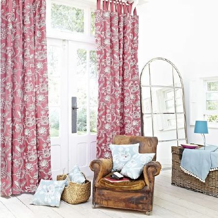 Prestigious Textiles -  Indigo Fabric Collection - Distressed leather armchair with blue and white cushions, red patterned curtains, a wicker basket and chest, blue lampshade and blue fabric