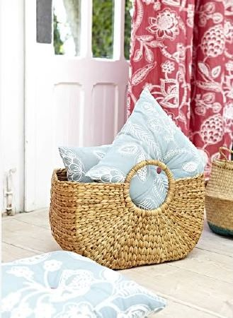 Prestigious Textiles -  Indigo Fabric Collection - Pale blue and white floral print cushions in a wicker basket, beside another wicker basket and red curtains with a large white floral print