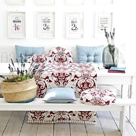 Prestigious Textiles -  Indigo Fabric Collection - White wooden table with bench seats, red and white patterned fabric and round cushions, blue cushions, wicker basket and a large glass vase