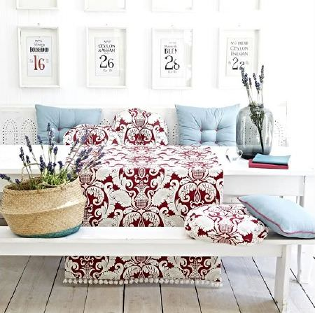 Prestigious Textiles -  Indigo Fabric Collection - Red and white fringed fabric and matching cushions, with blue cushions, a wicker basket and a grey glass vase, on a white bench style table
