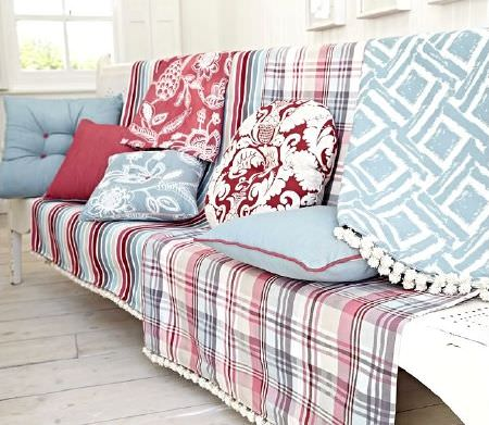 Prestigious Textiles -  Indigo Fabric Collection - Checked and patterned fabrics in red and blue, red and blue cushions, a blue and white patterned cushion, and a round red and white cushion