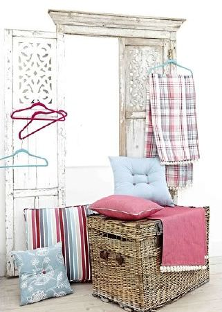 Prestigious Textiles -  Indigo Fabric Collection - Wicker chest, red fringed fabric, checked fabric, red cushion, blue cushion, blue floral cushion, striped cushion, red and blue coat hangers