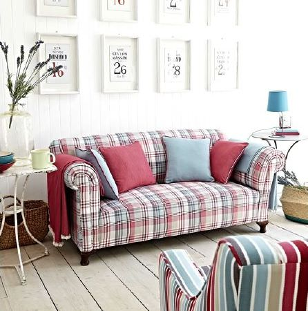 Prestigious Textiles -  Indigo Fabric Collection - Checked sofa, multicoloured striped armchair, red and blue cushions, wicker baskets, white rustic table, huge glass vase, blue lampshade