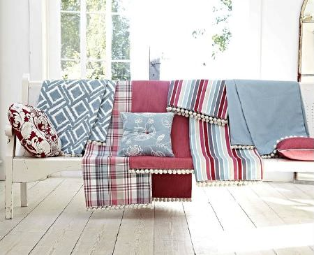 Prestigious Textiles -  Indigo Fabric Collection - White bench with fringed fabrics in blue and white, red, blue and white check, red, blue, multicoloured stripes, and three matching cushions