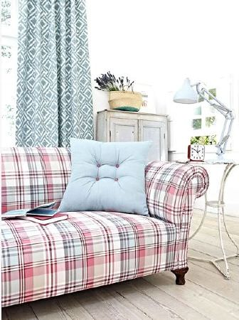 Prestigious Textiles -  Indigo Fabric Collection - Sofa covered in red and blue checks with a plain blue cushion, a white table, white lamp, wooden cabinet, clock, and blue and white curtains