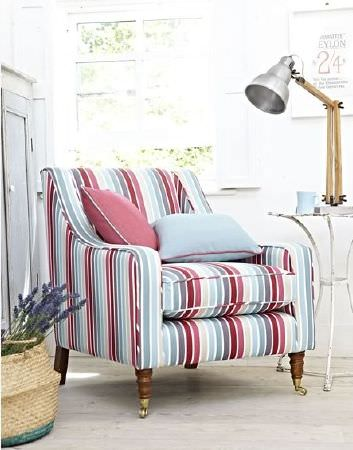 Prestigious Textiles -  Indigo Fabric Collection - Armchair with stripes in shades of red, blue and cream, with red and blue cushions, a wicker basket, and a metal and wood lamp on a table