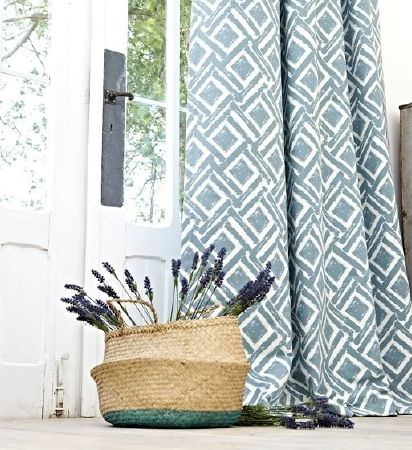 Prestigious Textiles -  Indigo Fabric Collection - Wicker basket with blue bottom. beside curtains which have a blue and white geometric print