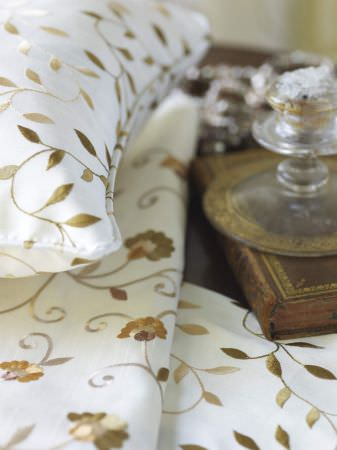 Prestigious Textiles -  Indulgence Fabric Collection - Classic white pillows with gold vine pattern and white fabric with gold carnation stitching